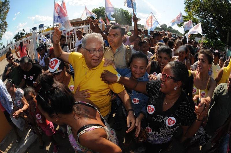 Amazonino caminha ao lado de multidão, em Carauari